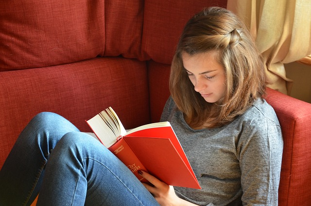 Girl reading a book on a comfy couch