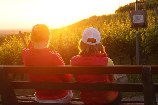 Two people sitting on a bench watching the sunset