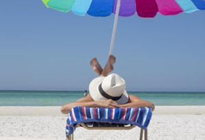Person sitting on the beach under an umbrella and on a lounge chair